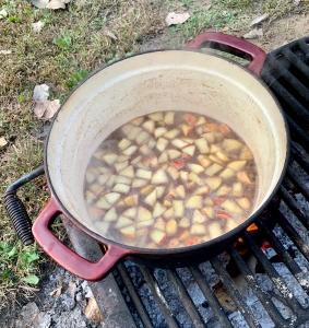 Apples cooking in liquid over fire.